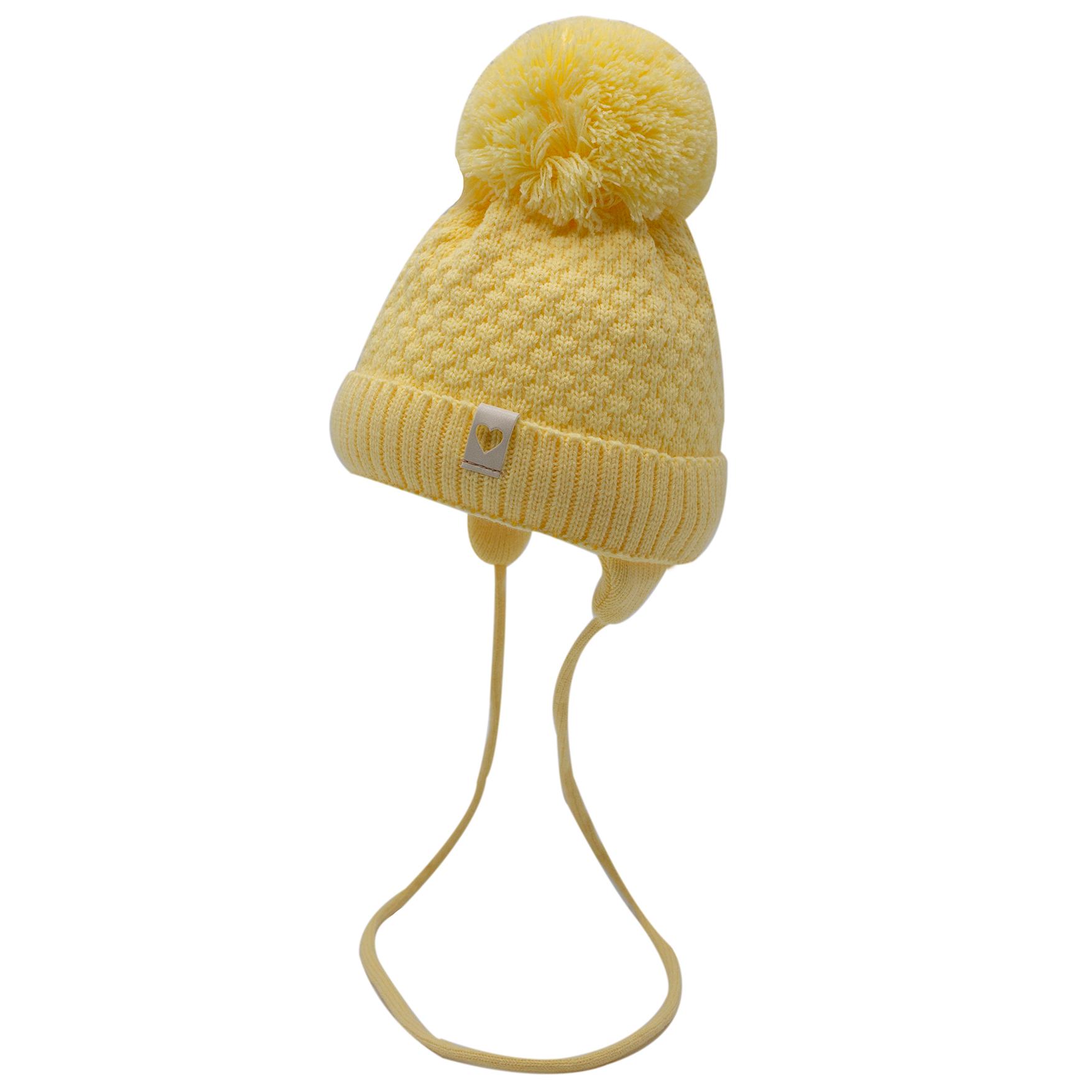 """Шапка """"Ажур"""" трехслойная с помпоном, с завязками и кожаным шевроном """"Сердечко"""". Цвет светло-желтый"""